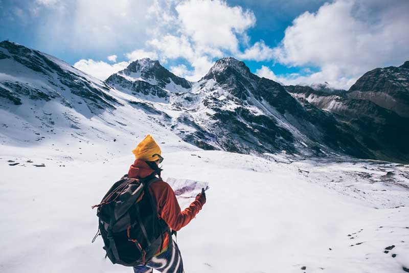 someone looking at a map on top of a snow capped mountain