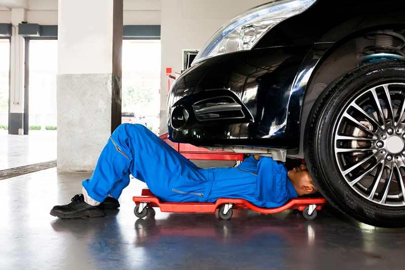 mechanic under a car bonnet