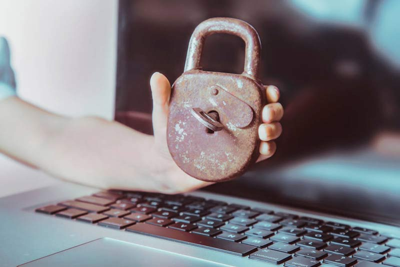 rusty padlock and key being help over a laptop